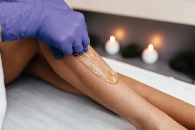 Primo piano della gamba di una donna estetista ceretta in beauty spa
