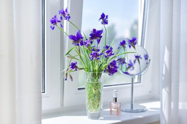 Primo piano di bellissime iridi viola blu in un vaso, profumo, specchio per il trucco sulla finestra.