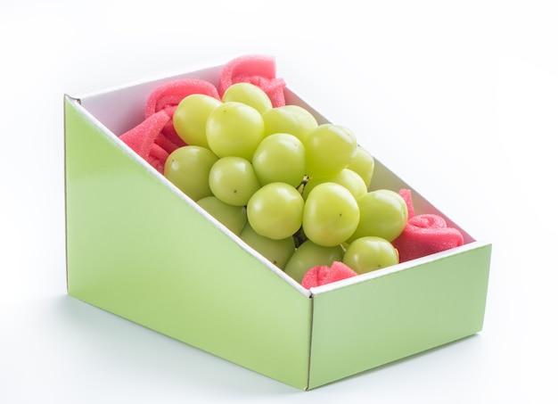 Chiuda in su dell'uva verde del moscato del santuario in scatola bella isolata su briciolo