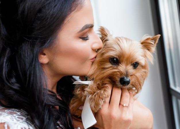 Primo piano di una bella sposa bruna che tiene tra le braccia e bacia uno yorkshire terrier