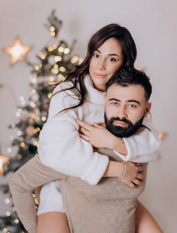 Primo piano di una bella bruna che abbraccia il suo ragazzo barbuto seduto sulla schiena sullo sfondo dell'albero di natale