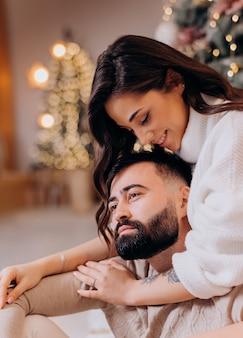 Primo piano di una bella bruna abbraccia il suo ragazzo barbuto e sorride