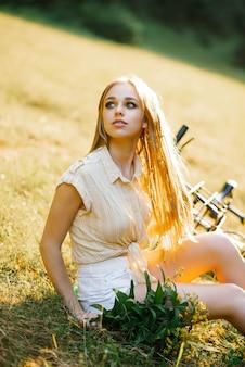Primo piano di una bella donna europea in abiti casual seduta su un prato e guardando lontano accanto a una bicicletta gialla su una passeggiata in campagna
