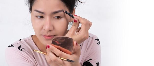 Primo piano di bel viso di giovane donna asiatica che ottiene trucco. artista sta applicando l'ombretto sul sopracciglio con pennello e matita. signora chiuse gli occhi con il relax
