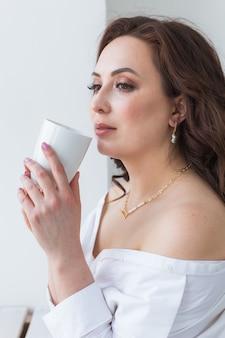 Primo piano di belle mani femminili che tengono grande tazza bianca di caffè cappuccino.