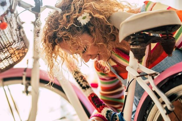 Primo piano di una bella donna caucasica felice che fa opere d'arte a casa con tessuti fatti a mano e bici vintage