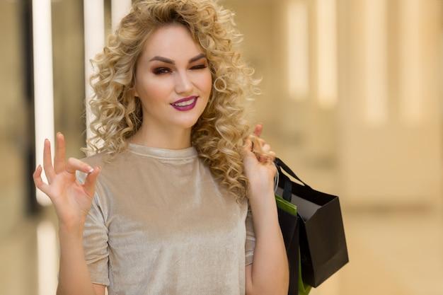 Chiuda in su di bella donna felice con i sacchetti della spesa che sorride e che mostra ok nel centro commerciale. concetto di acquisto