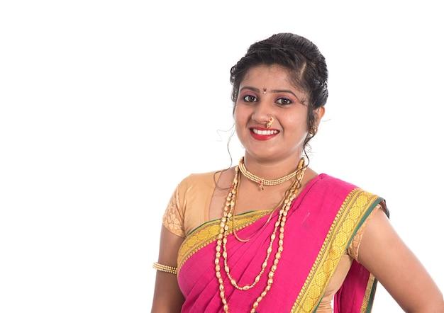 Primo piano di bella ragazza indiana tradizionale giovane in saree sul muro bianco