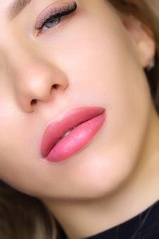 Primo piano delle belle labbra di una giovane modella con un tatuaggio sulle labbra