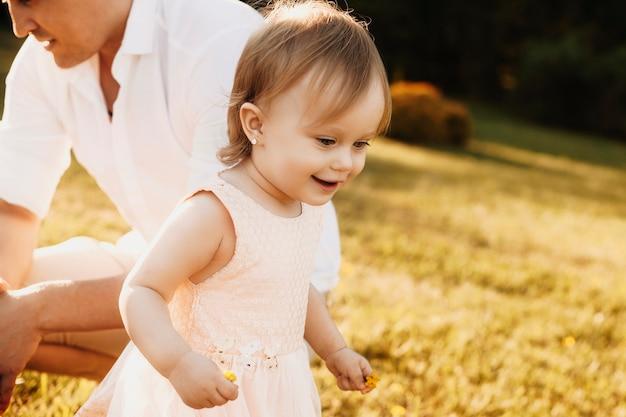 Primo piano di una bella bambina divertendosi all'aperto sorridente. bambino che corre e sorride nel cortile.