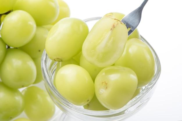 Primo piano del bellissimo santuario moscato verde uva in una tazza di vetro isolato su sfondo bianco, percorso di clipping tagliato.