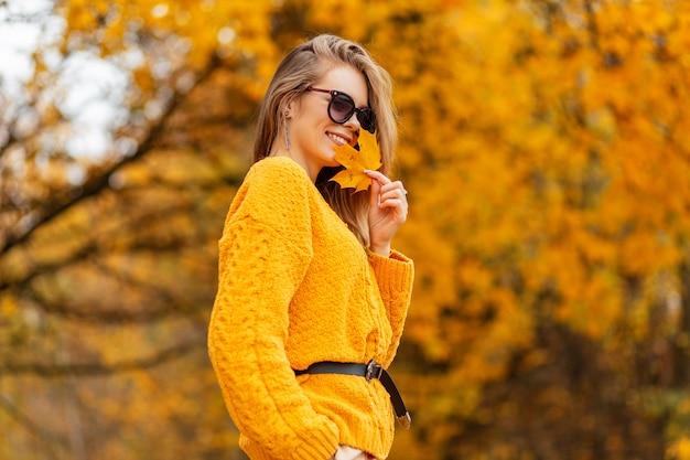 Chiuda in su della giovane donna bella sportiva sexy gambe in elegante gonna bianca in scarpe da ginnastica moda sulla natura. atleta ragazza moderna in abiti sportivi alla moda cammina sull'erba nel parco.