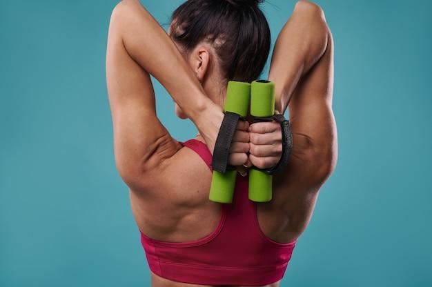 Primo piano di una bella e forte schiena muscolare di una donna snella che tiene i manubri e pompando i muscoli dei tricipiti