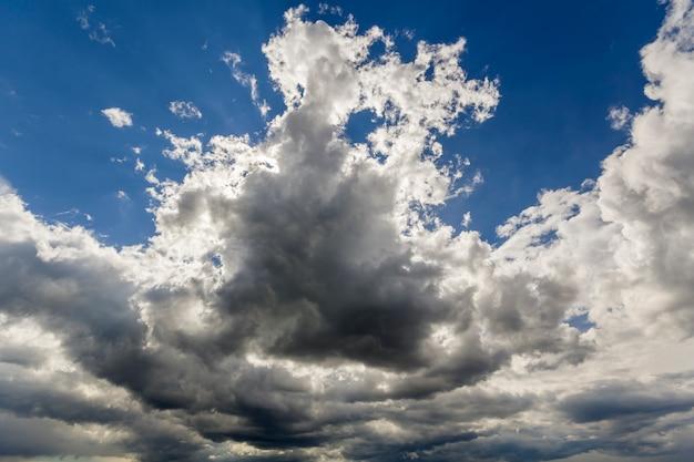 Bella vista del primo piano delle nuvole larghe scure grige bianche bianche variopinte illuminate dal sole che si sparge contro il cielo blu profondo che si muove con il vento. bellezza e potere della natura, meteorologia e concetto di cambiamento climatico.