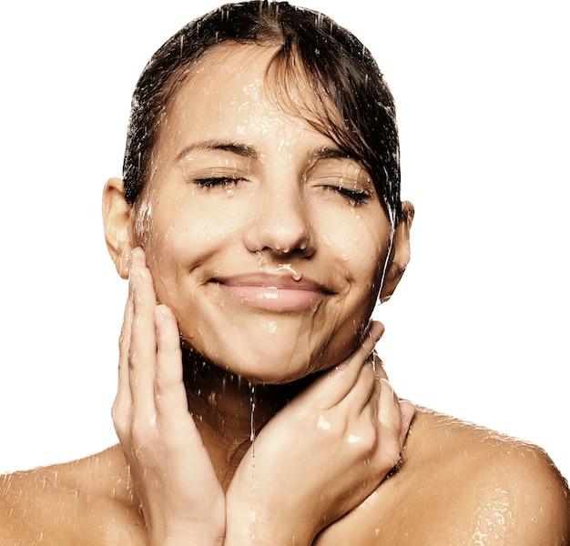 Primo piano del viso di bella donna bagnata con una goccia d'acqua