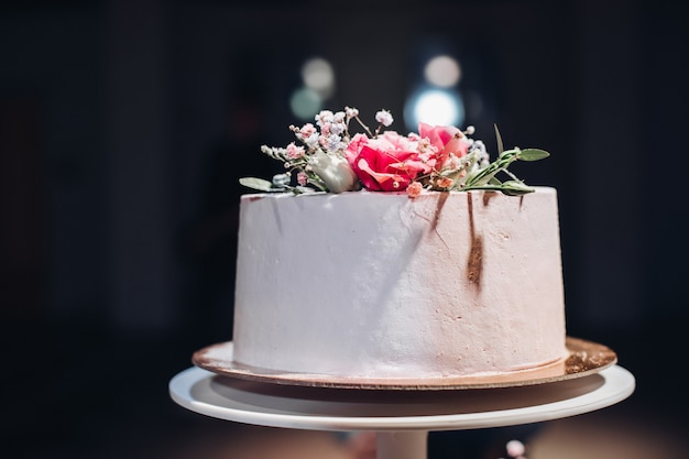 Primo piano di bella torta nuziale liscia bianca decorata con fiori secchi sulla parte superiore in luce artificiale.