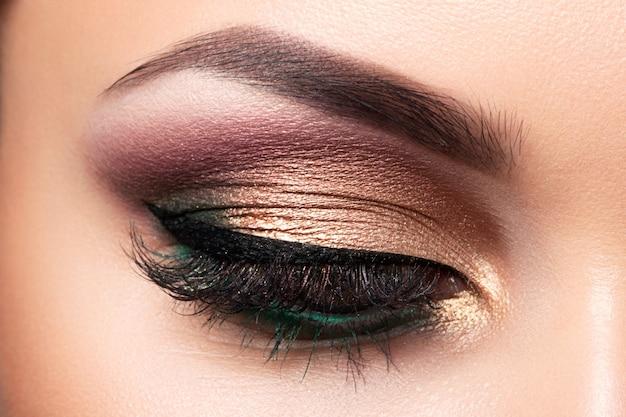 Chiuda in su dell'occhio di bella donna con trucco occhi smokey multicolore. trucco alla moda moderna.