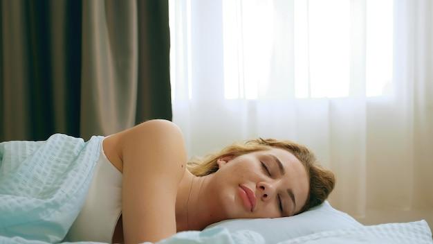 Primo piano di una bella donna che dorme bene in un letto comodo.