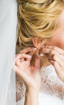 Primo piano di bella donna che indossa orecchini di diamanti lucenti