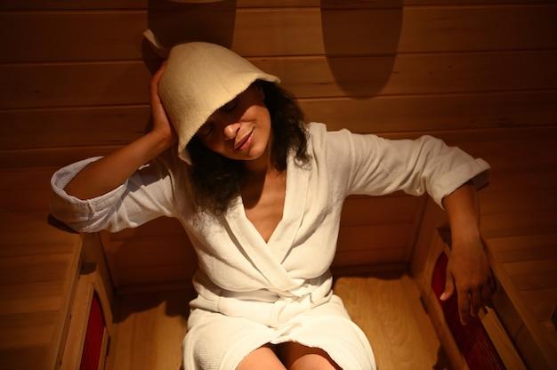 Primo piano di una bella donna con gli occhi chiusi che si gode la procedura spa nella sauna a infrarossi