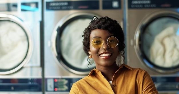 Chiuda su di bella giovane donna afroamericana in occhiali da sole gialli che sorridono allegramente alla macchina fotografica nella stanza di servizio della lavanderia. ritratto della ragazza abbastanza felice che ride con le lavatrici