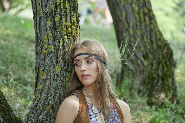 Close up bella giovane donna hippie in piedi vicino a un albero nella foresta