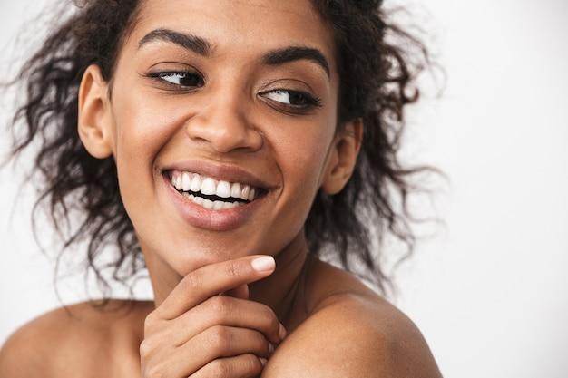 Primo piano di una giovane e bella donna africana in topless in posa su bianco