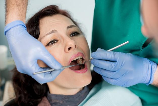 Chiuda in su di bella giovane donna che ha controllo dentale in su. dentista che esamina i denti di un paziente, che tiene gli strumenti dentali - specchio e sonda. odontoiatria.