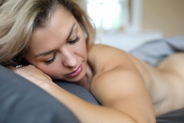 Il primo piano di bella giovane donna che dorme nudo sul letto di seta copre di mattina. colpo a macroistruzione della femmina rilassata sotto la coperta. sogni d'oro e concetto di riposo
