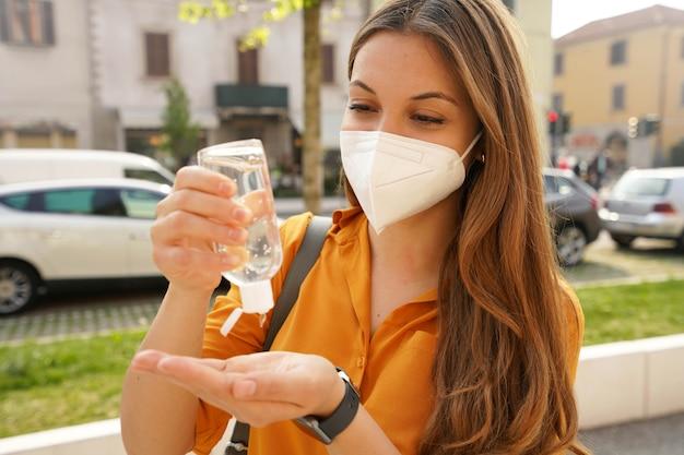 Primo piano di una giovane e bella donna che indossa la maschera protettiva kn95 ffp2 che utilizza gel alcolico che si disinfetta le mani in una strada cittadina. igiene e concetto di assistenza sanitaria.