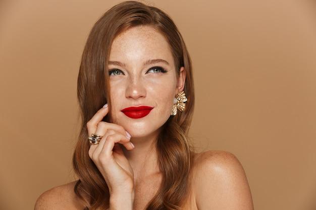 Primo piano di una giovane e bella donna che indossa il trucco e accessori per gioielli in posa isolato sul muro beige