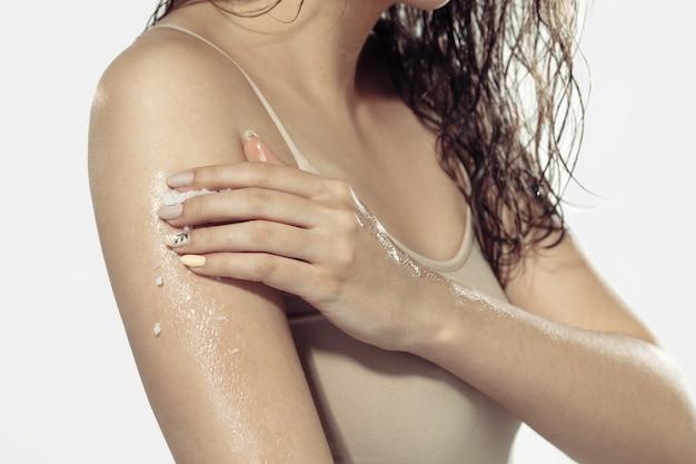 Primo piano di bella giovane donna su superficie bianca. pelle luminosa e sana
