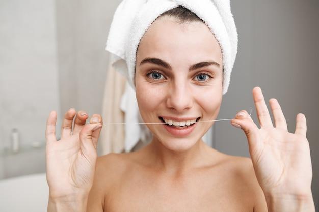 Primo piano di una giovane e bella donna con un asciugamano sulla testa in piedi in bagno, usando il filo interdentale