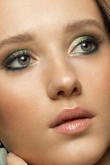 Foto di bellezza del primo piano di una bella ragazza con la pelle pulita e gli occhi espressivi.