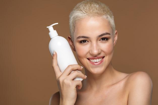 Ritratto di bellezza ravvicinato di una giovane donna bionda sorridente attraente con i capelli corti in posa isolata su marrone, che mostra un contenitore di plastica vuoto