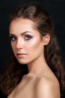 Chiuda sul ritratto di bellezza di giovane modello abbastanza mora con occhi smokey multicolori compongono la posa