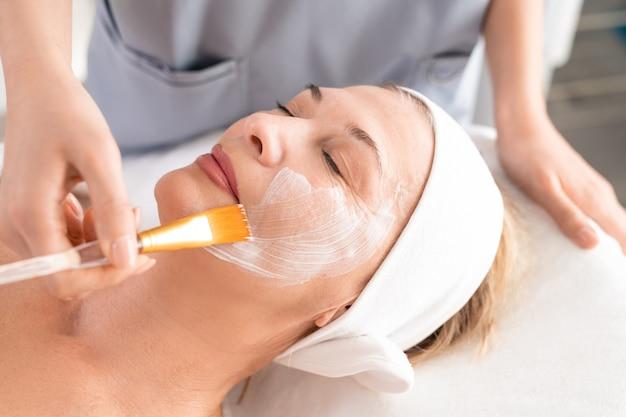 Primo piano del professionista di bellezza che applica maschera facciale alla donna matura rilassata con gli occhi chiusi alla procedura della stazione termale