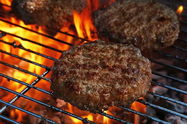 Primo piano di hamburger di carne di manzo o di maiale barbecue per hamburger preparati alla griglia su griglia a fiamma per barbecue, vista ad alto angolo