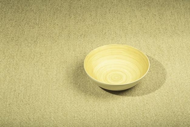 Primo piano sulla trama del tappeto beige con ciotola di legno