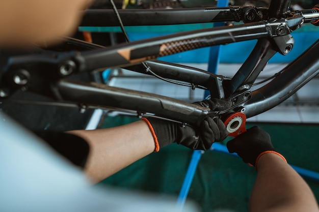 Primo piano di una mano di un meccanico di biciclette che utilizza una chiave del movimento centrale