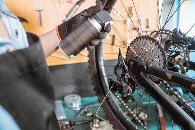 Primo piano delle mani dei meccanici della bicicletta nei guanti che tengono il flacone durante l'applicazione dello spray lubrificante