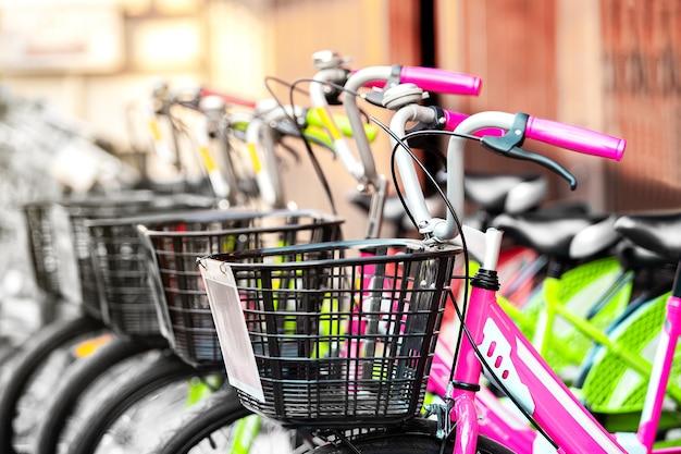 Primo piano di biciclette in fila con cesto su biciclette vintage e classiche presso il negozio per il noleggio e la vendita di biciclette per viaggi ed esercizio fisico in città urbana