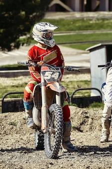 Primo piano del motociclista che si siede sulla motocicletta nel punto di partenza prima dell'inizio della gara
