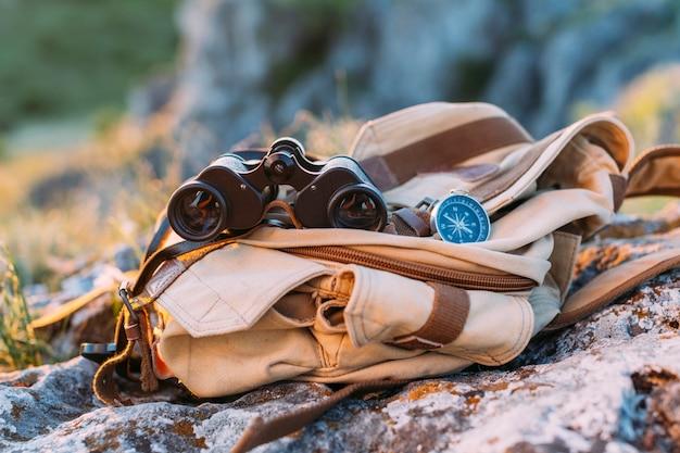 Primo piano del binocolo, della bussola e della borsa su roccia