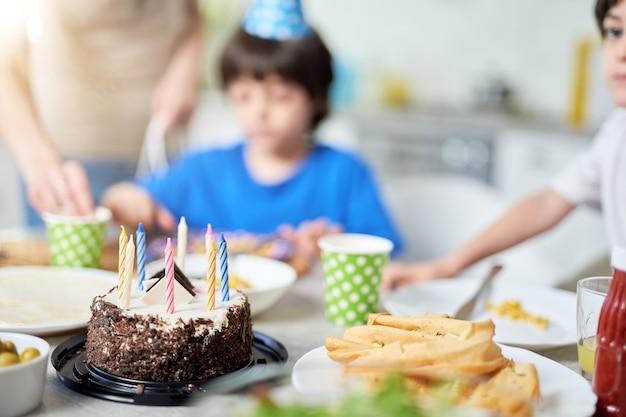 Primo piano di una torta di compleanno con candele sul tavolo. felice famiglia ispanica con bambini che festeggiano il compleanno a casa. messa a fuoco selettiva