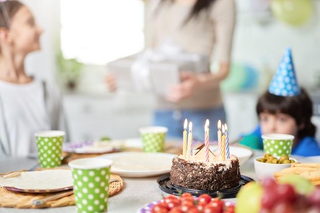 Primo piano di una torta di compleanno con candele sul tavolo. felice famiglia latinoamericana con bambini che festeggiano il compleanno a casa. messa a fuoco selettiva