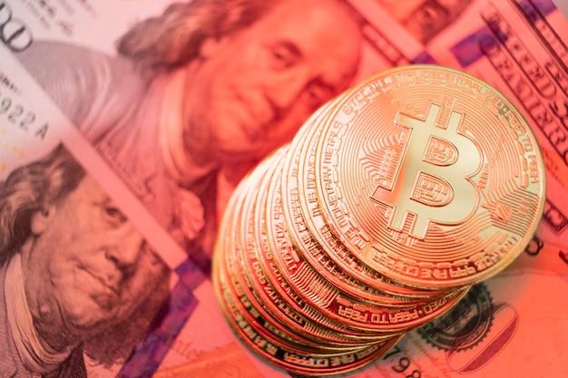 Primo piano sulla moneta bitcoin con illuminazione arancione, profondità di campo molto ridotta.