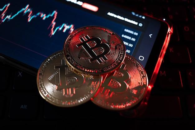 Primo piano sulla moneta bitcoin con illuminazione rossa che allude alla caduta della moneta, profondità di campo molto ridotta.