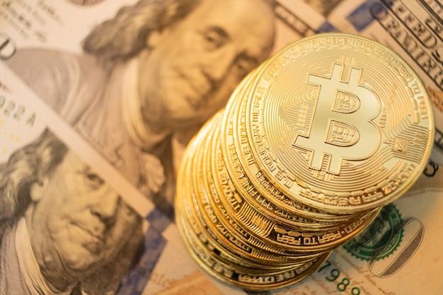 Primo piano sulla moneta bitcoin con illuminazione gialla, profondità di campo molto ridotta.