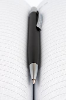 Avvicinamento. penna a sfera nera su un libro aperto.